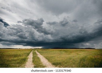 A road in the fields in front of stormy clouds