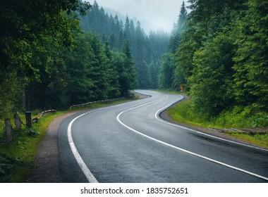 Straße im Nebelwald an regnerischen Tagen im Frühling. Schöne Gebirgsstraße, Bäume mit grünem Laub im Nebel und bewölkter Himmel. Landschaft mit leerer Asphaltstraße durch Wälder im Sommer. Reisen