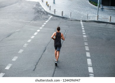 Road to the future. Rear view of handsome young man in sportswear jogging against industrial city view