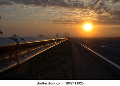 The road going into fog towards the rising sun