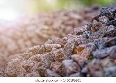 Road gravel and granite gravel texture. Crushed Gravel background. Pile of Stones texture. Industrial coals. Sun beam lights.
