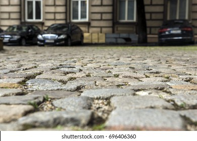 Road from gray paving stones to the background of a car