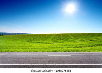 Road and green field with sun on blue sky. Landscape in springtime