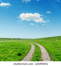 road in green grass and clouds in blue sky