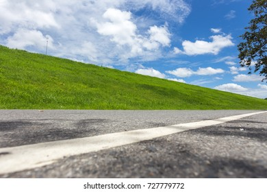 Road with green grass field under white clouds and blue sky.