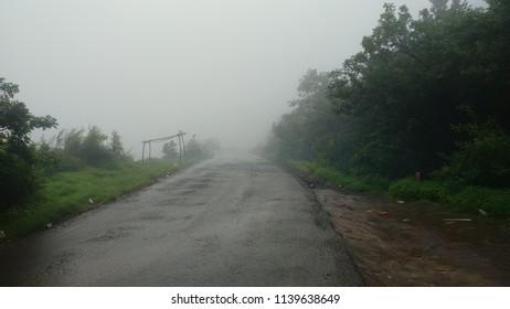 road with greenery fog mist in rain season