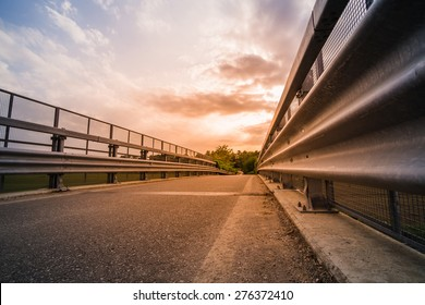 Road and guard rails at the sunset
