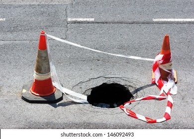 road hole with warning cones and tape