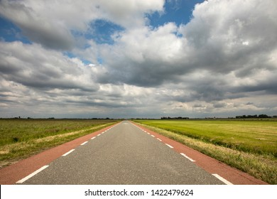 Road in Holland with red cycle path on both sides, perspective, under heavy dark threatening cloudy skies and between green meadows and a faraway straight horizon.