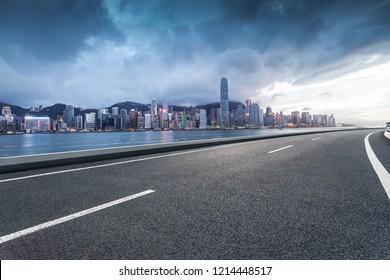 The road and the Hongkong skyline are at night.