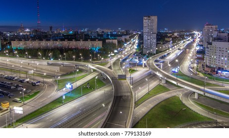 Road interchange of People Militia street, Mnevniki street and avenue Marshal Zhukov timelapse aerial top view in Moscow at night from rooftop. Traffic on the road with overpass