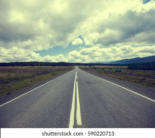 the road into the distance under a blue sky