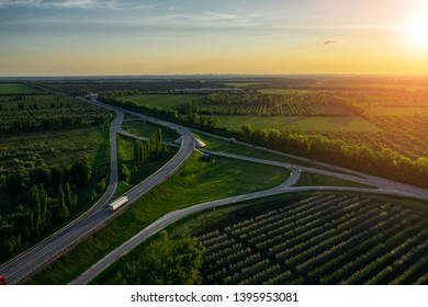 Road junction of speedy country highway route among green fields and trees with fast moving cars and trucks on background of beautiful dramatic sunset in warm summer evening, toned