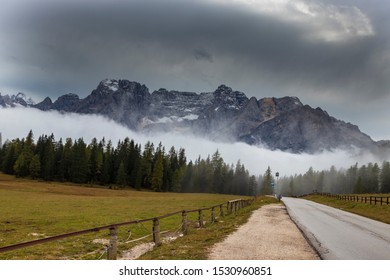 Road from Lake Misurina between the mountains of the Italian Dolomites to Cortina. The mountains are in the fog and there are clouds in the sky.