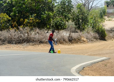 ROAD TO LAMPOUL, SENEGAL - APR 23, 2017: Unidentified Senegalese man stands near the road with packages of water nearby. Still many people in Senegal live in poverty