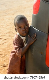 ROAD TO LAMPOUL, SENEGAL - APR 23, 2017: Unidentified Senegalese little boy leans on the bumper of the car. Still many people in Senegal live in poverty