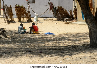 ROAD TO LAMPOUL, SENEGAL - APR 23, 2017: Unidentified Senegalese little girls sit on the ground in the shadow. Still many people in Senegal live in poverty
