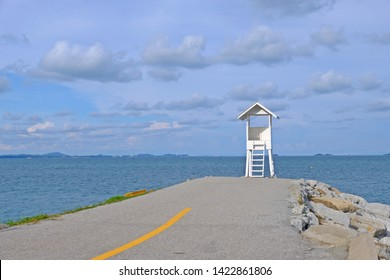 Road lead to little wooden white life guard tower at a far with blue sky background,  Khao Laem Ya–Mu Ko Samet National Park, Rayong province, Thailand.