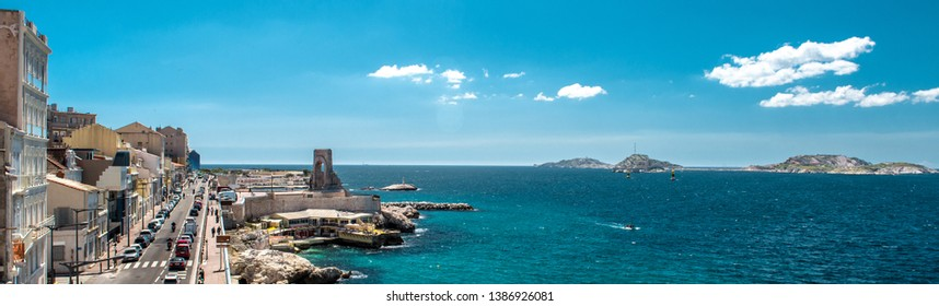 The road leading along the Plage des Catalans in Marseiile city, picturesque panoramic view turquoise Mediterranean Sea busy coastal highway, blue cloudy sky copy space, France
