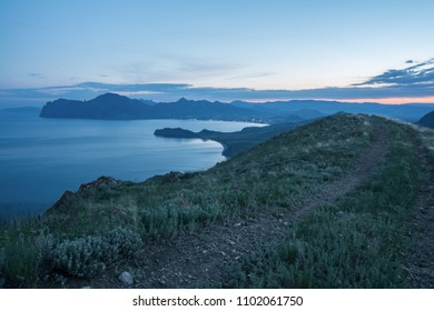 the road leading to the city through the mountains. evening landscape after sunset