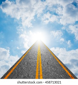 Road leading to the cloudy sky and the sun shining bright light at the end of the road. Representing success, religion, holy, faith, belief, spiritual concept