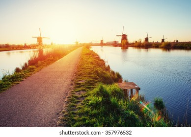 The road leading to the Dutch windmills from the canal in Rotterdam. Holland. Netherlands