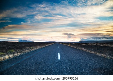 Road leading into the distance under a dramatic sky