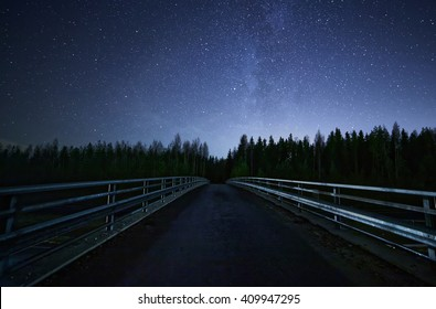A road leading into night sky full of stars and visible milky way. A Bridge and dark forest on the foreground.