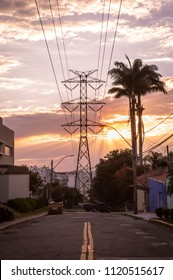 Road leading to palm trees and power line tower silhouettes against the sunset