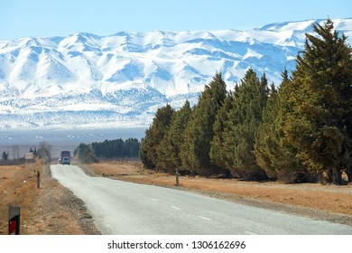 Road leading to the snow-capped Atlas mountains, Morocco, Africa