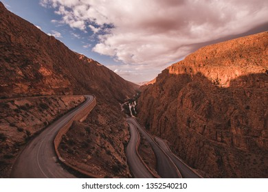 Road leading through a beautiful valley in the Atlas Mountains with a small river in the background under a blue and cloudy sky, in Morocco
