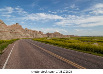A road leads into the dramatic landscape of Badlands National Park with yellow super bloom wildflowers on the right and large eroded dirt formations on the left.