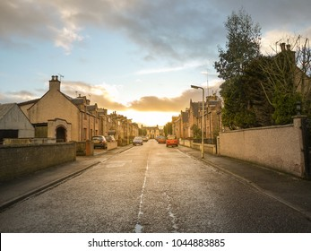 A road leads to a quiet residential neighbourhood area with traditional British style houses during sunset. Inverness, Scotland, United kingdom
