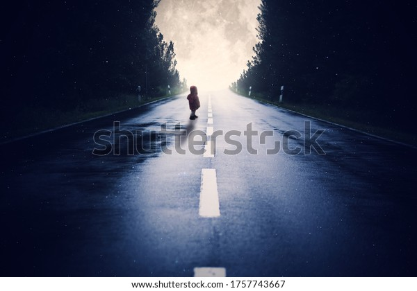 Road leads through the forest during a full moon night. Child stands on the street by full moon