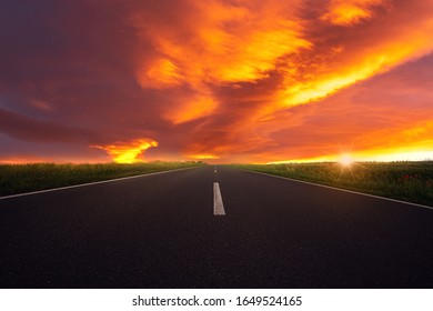 A road leads towards the sunset. Red sky with clouds