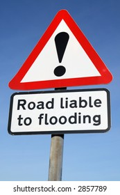 Road liable to flooding warning sign and a blue sky.