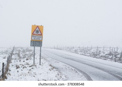 'Road liable to icing' sign on snowy road in the Campsie Fells, Stirling, Scotland, UK - with copy space