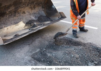the road maintenance worker throws the old asphalt into the excavator's bogie in road construction