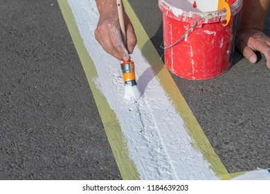 Road marking is applied by hand with a brush