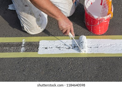 Road marking is applied by hand with a paint roller