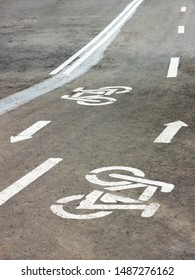 The road marking of the asphalt bicycle lane in the city park.