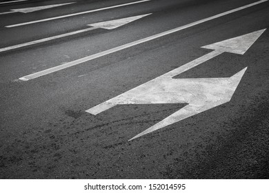 Road marking with white lines and arrows on dark asphalt