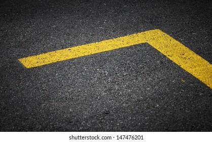 Road marking with yellow lines on dark asphalt