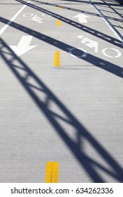 Road markings with arrows and bike path. Bicycle route with shadows in the evening.