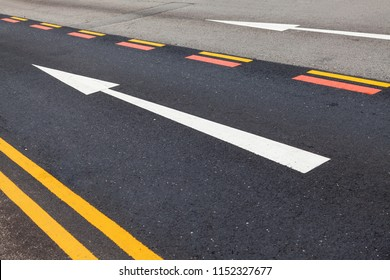 Road markings on the asphalt. Painted signs on the roadway for vehicle drivers. Dotted line and arrows. Singapore.