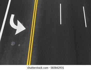 Road markings on asphalt on the street of Manhattan in New York City. Iridescent spot of gasoline on asphalt