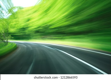 Road in motion blur at green forest