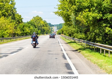 Road with motorcycle and cars in traffic