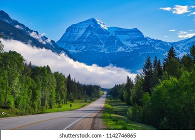 Road to Mount Robson. Low hanging clouds. Road through the forrest. Beautiful blue sky in the Rocky Mountains.