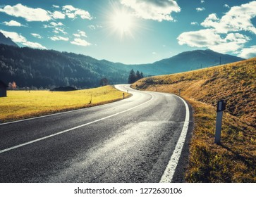 Road in mountain valley at sunny morning in Dolomites, Italy. View with asphalt roadway, meadows with green grass, mountains, blue sky with clouds and sun. Highway in fields. Trip in europe. Travel